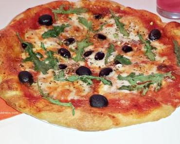 Selbstgemachte Pizza mit Ruccola-Oliven-Mozarella