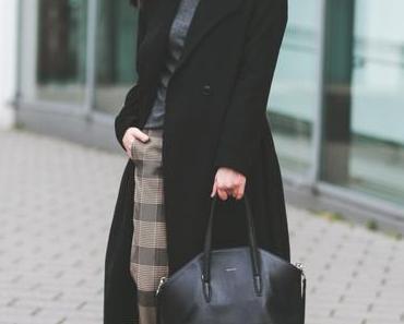 Winter Outfit mit karierter Bundfaltenhose, New Era Cap und schwarzem Wintermantel