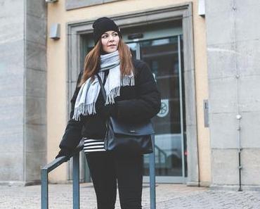 Winter Outfit mit schwarzer Puffer Jacke, grauem Schal und Samsøe & Samsøe Mütze